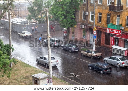 ODESSA, UKRAINE - June 6, 2014: Heavy rains and hail hit the Ukraine. Passers-by are hiding from the rain. Taken from the top point. #291257924