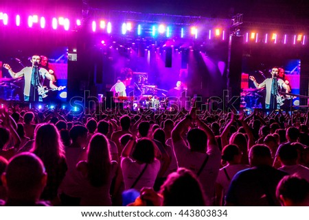Odessa, Ukraine - June 25, 2016: Large crowd of spectators having fun at stadium, at concert of Ukrainian group Ocean Elzy during creative light and music show. Cheerful bright show in party club #443803834