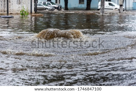 Odessa, Ukraine - May 28, 2020: driving car on flooded road during flood caused by torrential rains. Cars float on water, flooding streets. Splash on car. Flooded city road with large puddle Foto stock ©