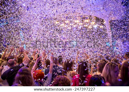 Odessa, Ukraine - May 31, 2014: Large crowd of people having fun in a nightclub at a concert during the creative light and music show. Cheerful young people showered great candy on club party. #247397227