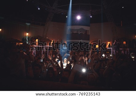 Odessa, Ukraine May 23, 2014: Night club dj party people enjoy of music dancing sound with colorful light, smoke machine, lights show and dance show. Hands up in the earth. - Shutterstock ID 769235143