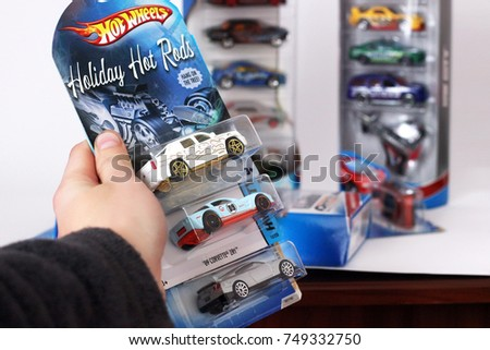 Odessa, Ukraine - November, 2017: Hot Wheels in a hand on a background of other toys on a white background. Kids toys. Machines. #749332750