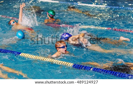 ODESSA, UKRAINE -24 September 2016: sporting swimming in pool during Ukrainian championship triathlon athletes among children. Children swimming competition in indoor pool #489124927
