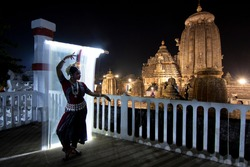 Odissi dancer dance recital against the backdrop of at Lingaraja Temple with light painting behind.