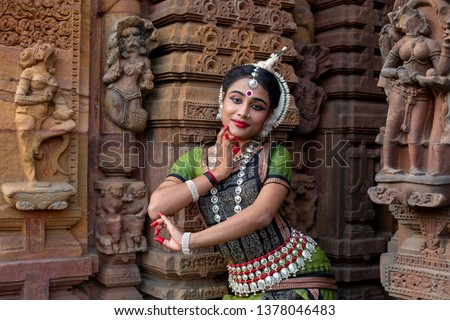 Odissi dancer striking pose against the backdrop of Mukteshvara Temple with sculptures in bhubaneswar, Odisha, India #1378046483