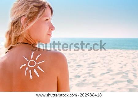 of sun cream on the female back on the beach #202986418