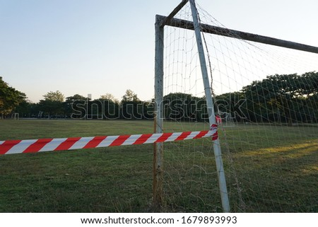 Photo of Off limits football field due to Corona virus pandemic outbreak. Red and white tape tied to a goal post to block off entry onto a football field.