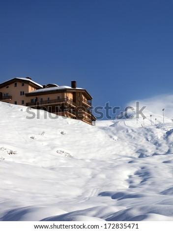 Off-piste slope and hotel at sun day. Caucasus Mountains, Georgia. Ski resort Gudauri. - stock photo