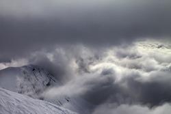 Off-piste slope and snowy rocks in bad weather. Georgia, ski resort Gudauri. Caucasus Mountains.