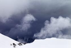 Off-piste slope and storm gray clouds. Caucasus Mountains, Georgia, ski resort Gudauri.