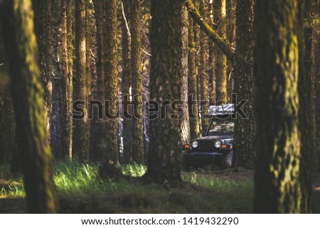 Off road adventure with a trendy 4x4 car in the forest. Offroad trip for a group of friends with camping tent on the roof Vintage cross-country vehicle Leisure adventurous open air holiday concept. #1419432290