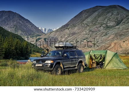 Off-road car camping with a tent among the mountains and clear blue sky.