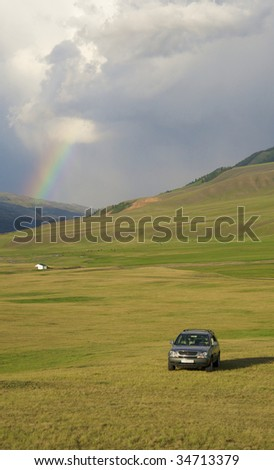 Off-road car highly in mountains against a beautiful rainbow