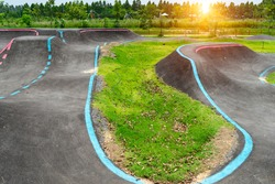 Off-Road Cycling Course.Asphalted bicycle pump track, racing speed track with traffic lines for  BMX racing track or Bicycle Motocross and Roller skating around with tree and sunlight background.