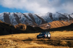 Off-road roadtrip travel on car on mountain road against rocks and glacier in Caucasus, Georgia. Beautiful lights and colors at sunset