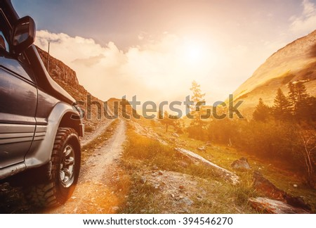 Off-road travel on mountain road. Beautiful mountains sunset