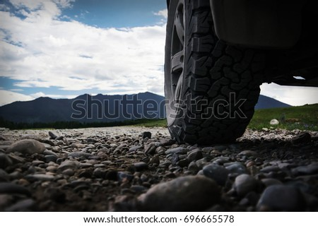 Off-road travel on mountain road. The wheel of the SUV in the foreground, on the stone road of gravel.