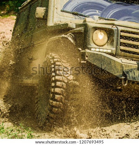 Off-road travel on mountain road. Travel concept with big 4x4 car. Mud and water splash in off-road racing. Motion and power concept #1207693495