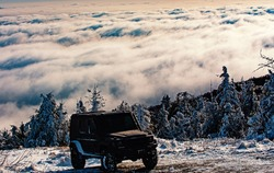 Off-road travel on snow mountain road. Winter ravel concept with 4x4 car. Jeep offroad outdoors adventures