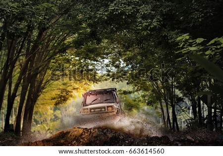 Off road vehicle coming through the trees tunnel.Travel and racing concept for four wheel drive off road vehicle . #663614560