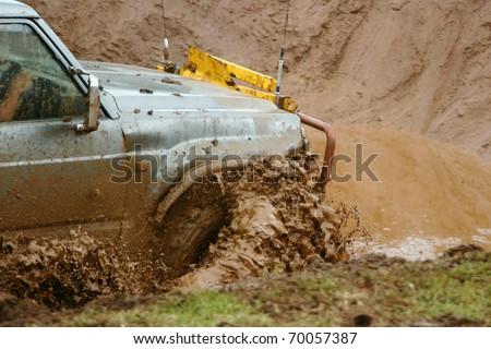 Off road vehicle going through a muddy water hazard.