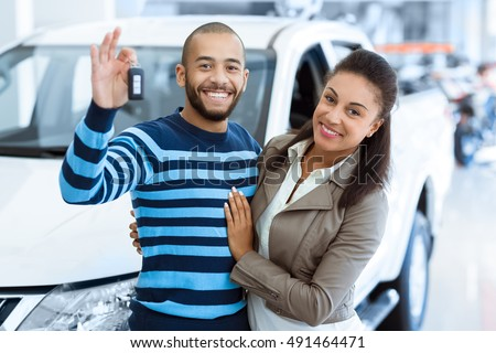 Off we go. Portrait of a happy mature couple smiling to the camera cheerfully posing near their newly bought car at the dealership handsome man holding out the car keys while embracing his wife