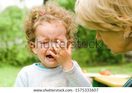 offend the child. children's tears, moods. resentment. comfort, feel sorry for the baby.  crying, hopelessness, despair, sobbing. grandmother pities little girl. human emotions. soft focus Stock photo ©