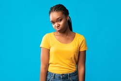 Offended African American Girl Sulking Looking At Camera Standing Over Blue Background. Studio Shot
