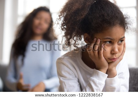 Offended African American preschooler girl looking in distance, holding head in hands, talking mother on background, family conflict, child punishment, complicated relationships with parent, close up