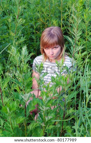 Offended by a sad girl sitting and hiding in the tall grass in the summer, Domodedovo, Moscow Region, Russia