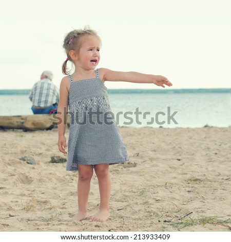 offended crying little girl on the beach. sad little girl with blond hair