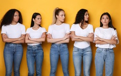 Offended Discontented Multiracial Ladies Looking At Asian Female Friend Unfriendly Disapproving Her Posing Crossing Hands Standing Over Yellow Studio Background. Adult Bullying And Racism