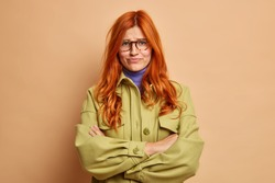 Offended dissatisfied redhead young woman keeps arms folded waits for explanations from boyfriend has hurt feelings dressed in fashionable green jacket smirks face poses against brown background