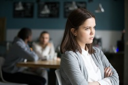 Offended frustrated millennial woman feeling upset suffering from loneliness having no friends or boyfriend sitting alone in cafe, sad social outcast or loner girl thinking of problem in public place