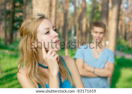 Offended girl with a boy at the background