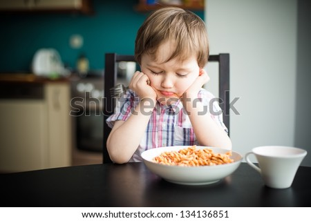 Offended little boy during eating  spaghetti at dinner
