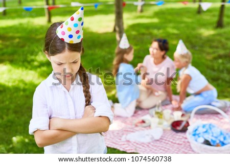 Offended little girl in birthday cap crossing her arms on chest while her friends talking to their teacher on background #1074560738