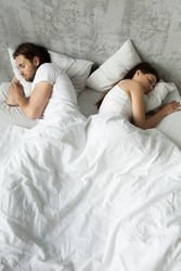 Offended lovers sleep separately in bed back to back, young lovers have sexual problems, avoid intimacy in bed, indifferent couple not talking after fight. Concept of bad relationship, no sex