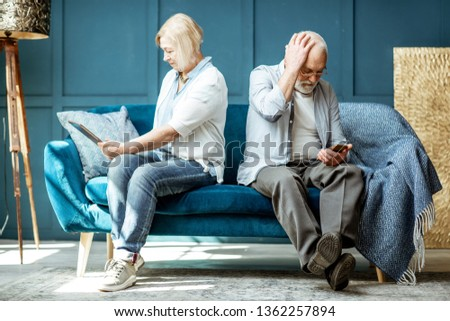 Offended senior man and woman sitting back to each other, using digital gadgets on the couch at home