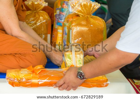 Offering (Donation) of saffron robes to Buddhist monk. Offering cloth for buddhist monk.eight necessities of a Buddhist monk. three vestments of a Buddhist monk - Shutterstock ID 672829189