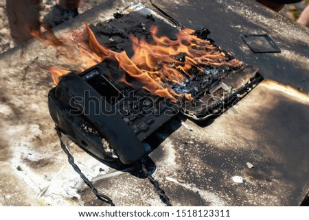 office accident. danger of smoking in the workplace. Burnt workplace. The consequences of a fire, a burned table, laptop and telephone. insurance guarantee loss coverage #1518123311