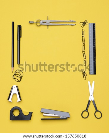Office and back to school supplies on a yellow background. Looking down on the all black and chrome tools from an overhead angle. The items are arranged in a rectangle forming a frame.