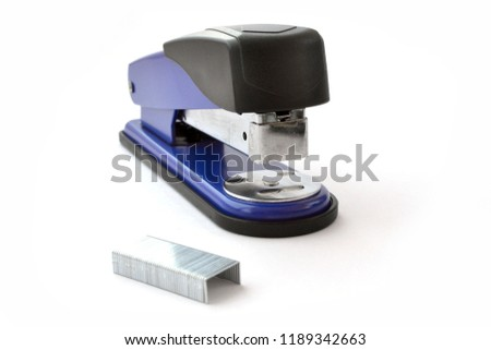 Office background with staples and stapler on white.