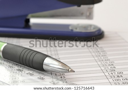 Office background with table, ruler, pen and stapler.