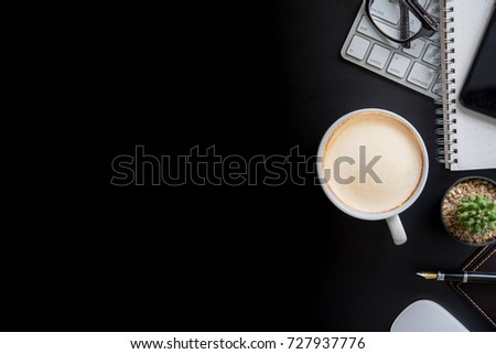 Office black desk table with computer, supplies and coffee cup. Top view with copy space