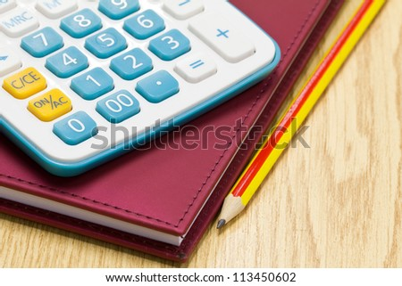 Office book with a pencil and a calculator on a office table.