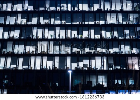 Office Building At Night. Late night at work. Glass curtain wall office building. Office building exterior in the late evening with interior lights on. Evening facade of an office building.