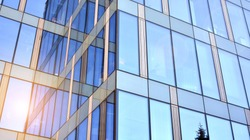Office building, details of blue glass wall and sun reflections.