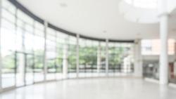 Office building or university lobby hall blur background with blurry school hallway corridor interior view toward empty corridor entrance, glass curtain wall, floor and exterior light illumination