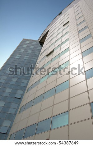 Office building with a hinged facade. Part of the facade opaque aluminum panel, part of - a complete glazing. Against the background of blue sky. Vertical orientation. - stock photo